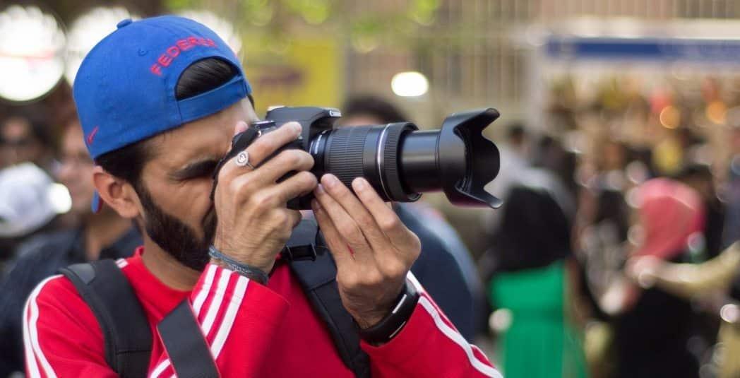 Mann fotografiert mit Teleobjektiv vor einer unscharfen Menschenmenge